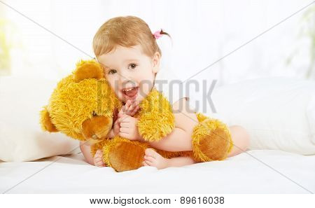 Cute Little Child Girl Hugging Teddy Bear In Bed