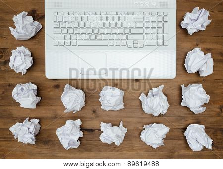 Laptop, sheets of paper and crumpled wads on table.
