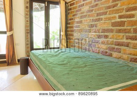 A Single Bed  Beside Brick Wall Background