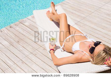 Woman sunbathing in chair by the pool