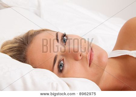 Woman Lies Awake In Bed. Sleepless And Thoughtful.