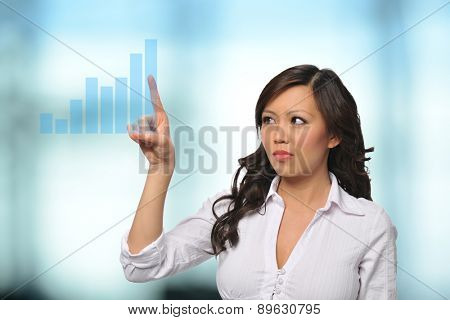 Asian Businesswoman with virtual touch screen inside an office building