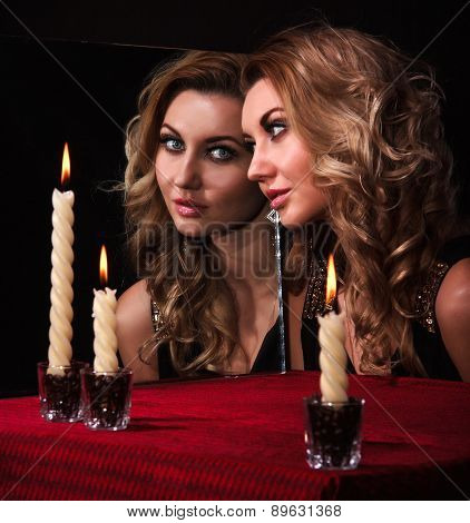 Beautiful Young Woman Looking In The Mirror Near Three Candles