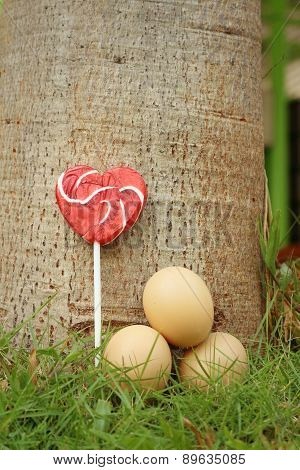 Eggs With Candy On A Green Grass.
