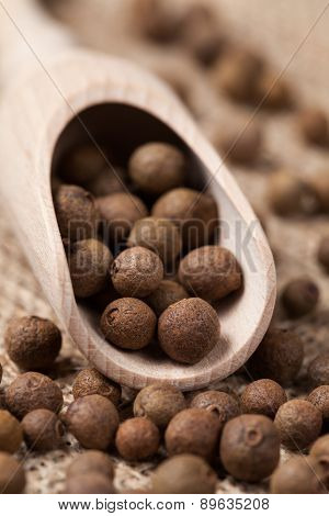 Allspice pepper flavour spice seeds in wooden spoon on textile b