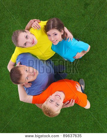 Group of young people lying on green grass.