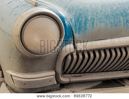 Dusty Old Blue Car Bumper And Headlight