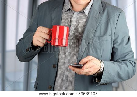 Young Businessmen Standing  With Coffee In The Office And Holding The Mobile Phone