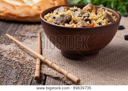 Traditional healthy asian national spicy rice food pilaf cooked with fried meat, onion, carrot and g
