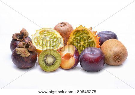 Various fruits: kiwano, mangosteen, plums and kiwi on white background