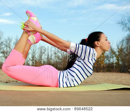 Young Woman Making Fitness And Yoga Exercises On Sand Beach Of The River