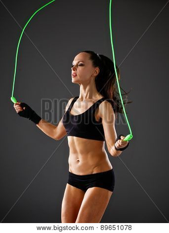 Full length view of an attractive woman with jumping rope.