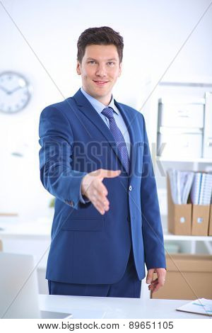 Business and office concept - businessman with open hand ready for handshake.