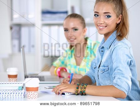Two women working together at office, sitting on the desk.