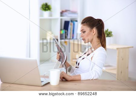 Cute businesswoman holding newspaper sitting at her desk in office.