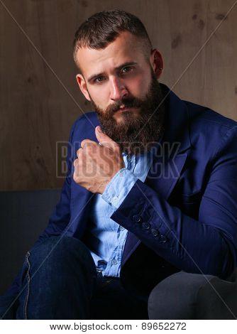 Businessman sitting on sofa in office lobby.