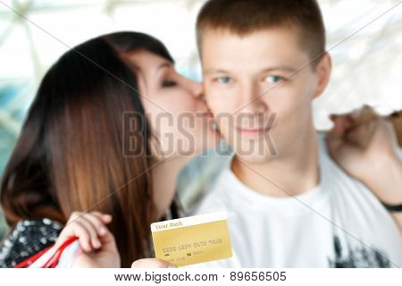 Young Couple With Purchases In Shopping Mall