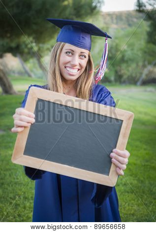 Excited Young Woman Holding Diploma and Blank Chalkboard Wearing Cap and Gown Outdoors.