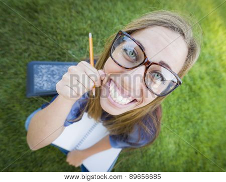 Fun Wide Angle Portrait of Pretty Young Woman with Books and Pencil Sitting in the Grass Outdoors.