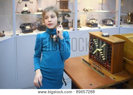 MOSCOW - APR 05, 2014: Girl in a blue jacket with old handset in the Museum of the History telephone in Moscow