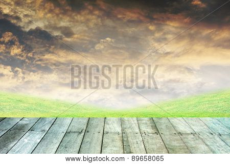 Green Grass And Orange Sky With Wooden Paving.