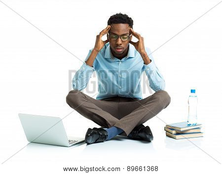 African American College Student In Stress Sitting With Laptop, Books And Bottle Of Water On White