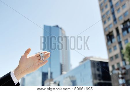 Man Hand Holding Keys, On Background Office Buildings