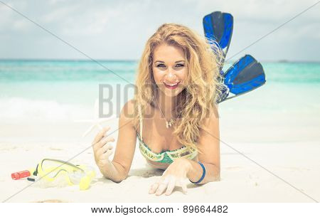 Woman Lying On The Sand Holding Starfish And Wearing Fins.