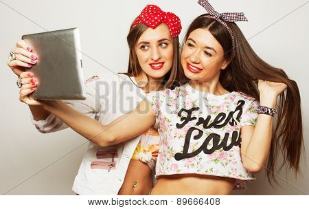 Two pretty young women wearing summer outfit and taking a self portrait with a tablet/ Studio shot over grey background.