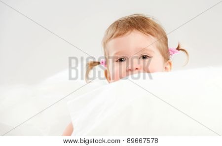 Little Girl Peeping From Of Pillows In Bed