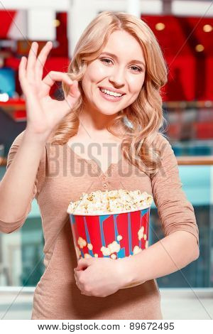 Woman with popcorn showing OK