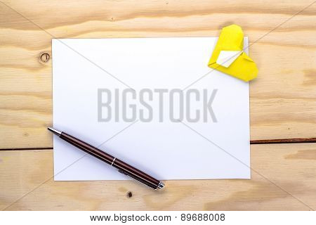 yellow origami heart and  pen on white paper sheet for love letter.