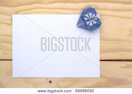 blue origami heart and white paper sheet for love letter.