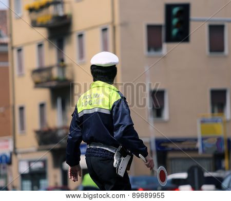 Italian Policeman In Uniform While Blocking Traffic With The Red Paddle