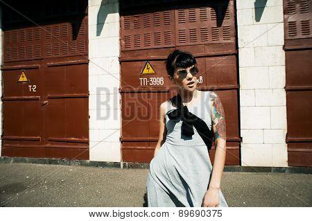 tattooed lady wears sunglasses in backyard
