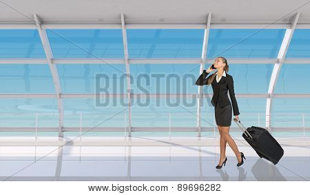 Flight attendant talking on mobile in airport