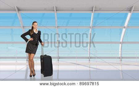 Flight attendant standing with luggage in airport