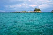 foto of albania  - Rocky island in the Ionian sea and the mountains in Albania - JPG