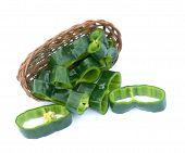 stock photo of poblano  - sliced poblano pepper on bamboo basket on white background - JPG
