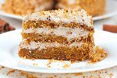 stock photo of sponge-cake  - Piece of homemade tasty carrot sponge cake with pastry cream on white plate - JPG