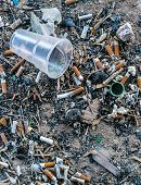 picture of butts  - Rubbish cig butts and a plastic drinking cup rest on an empty factory building floor - JPG