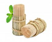 stock photo of bundle  - Two bundles of toothpicks in packs of straw and a small sprig of mint isolated on white background - JPG