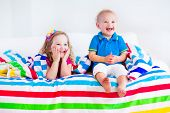 foto of little young child children girl toddler  - Two kids sleeping in bed under colorful blanket - JPG