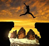 stock photo of gap  - Silhouette the girl jumping over the gap at sunset in the background  Tre Cime di Lavaredo - JPG