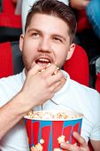 pic of greedy  - It is all mine. Young man greedy eating popcorn in cinema while watching film. ** Note: Shallow depth of field - JPG