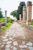 stock photo of interlocking  - Decumanus road in Ostia old town Rome Italy topped with interlocking stones - JPG