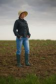 pic of farm land  - Portrait of Adult Female Farmer Standing on Fertile Agricultural Farm Land SoilLooking into Distance - JPG