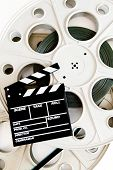 pic of mm  - Movie clapper on two 35 mm cinema reels with film vertical frame on white background - JPG