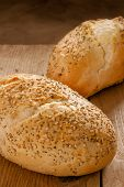 stock photo of seed  - Rustic seeded baguettes small freshly baked bread rolls crusted with poppy and sesame seeds - JPG