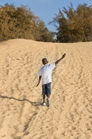 pic of ten years old  - Afro boy walking in the sand - JPG